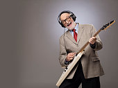 Happy funny senior man playing electric guitar