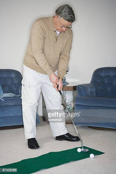 Senior man playing golf in the living room