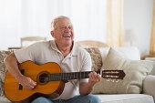 Senior man playing guitar, Jersey City, New Jersey, USA