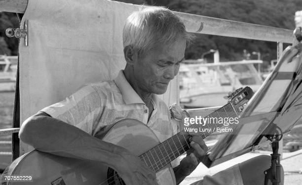 Senior Man Playing Guitar While Sitting Against Railing