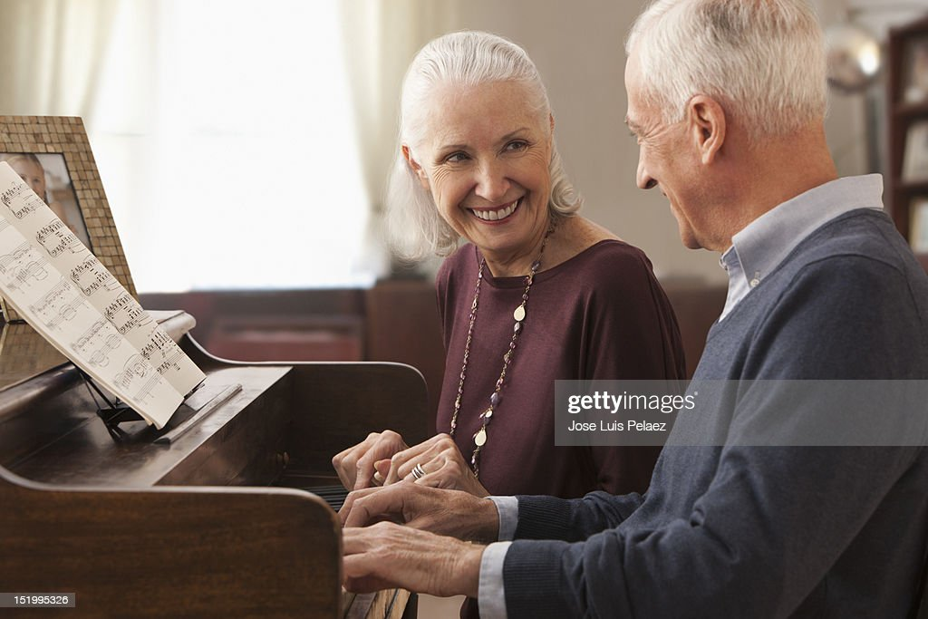 Senior man playing piano for wife : Stock Photo