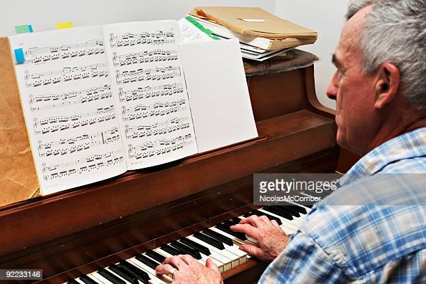 Senior uomo che suona musica classica al pianoforte pezzo