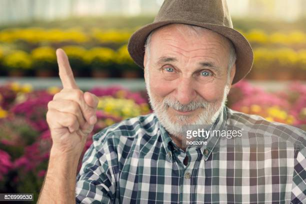 Senior man pointing with his finger at greenhouse