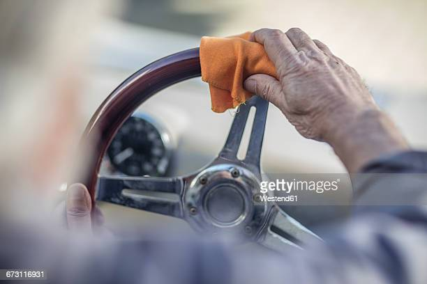 Senior man polishing steering wheel of a car