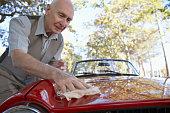 Senior Man Polishing the Hood of His Car