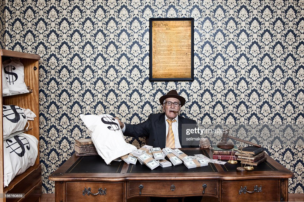 Senior man posing with US constitution, gavel and money bags : Stock Photo