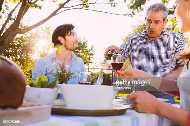 Senior man pouring red wine into glasses of couple having dinner in garden