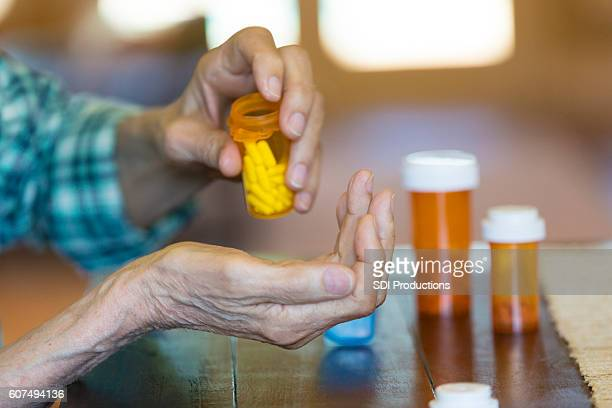 Senior man pours medication into wife's hand