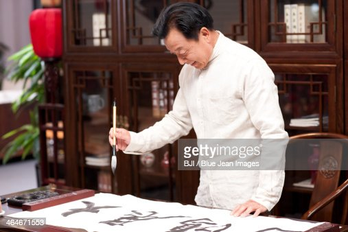 Senior man practicing calligraphy in the study