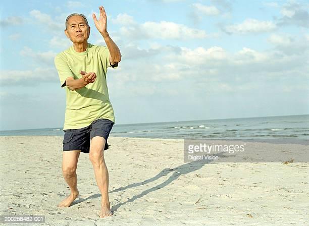 Senior man practicing tai chi on beach