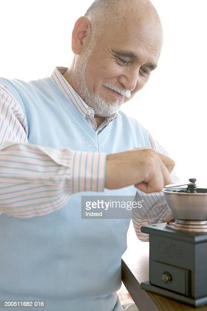 Senior man preparing coffee using mill grinder, smiling,