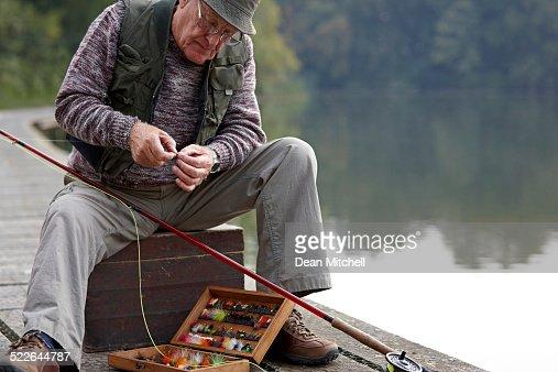 Idoso a preparar o isco para pesca