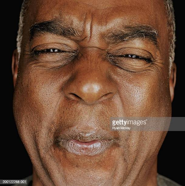 Senior man puckering lips and squinting eyes, portrait, close-up