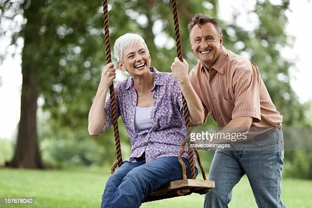 Uomo anziano, spingendo la moglie su un Altalena