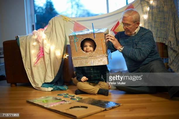 Senior man putting robot costume on grandson