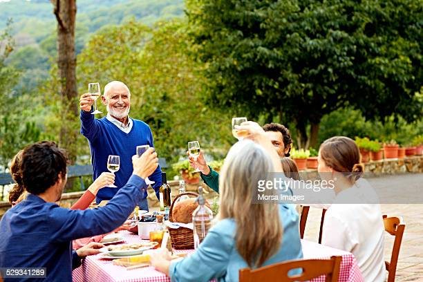 Senior man raising toast to family at meal table