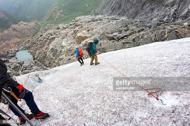 Senior man rappelling down icy glacier