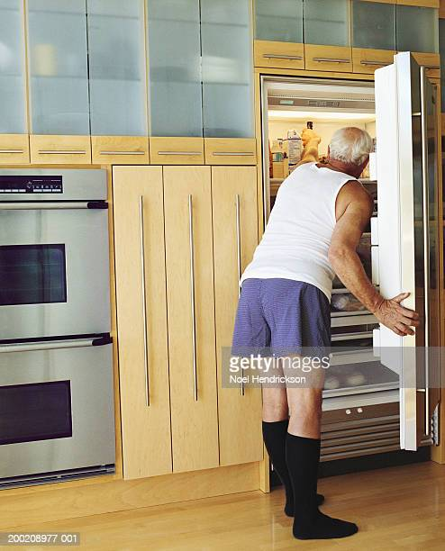 Senior man reaching into refrigerator, rear view