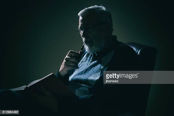 Senior Man Reading a Book in Dimly Lit Room