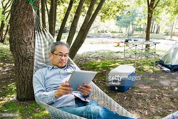 読書する老人男性、デジタルタブレットのハンモック