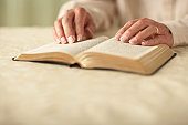 Senior man reading Bible, close-up of hands