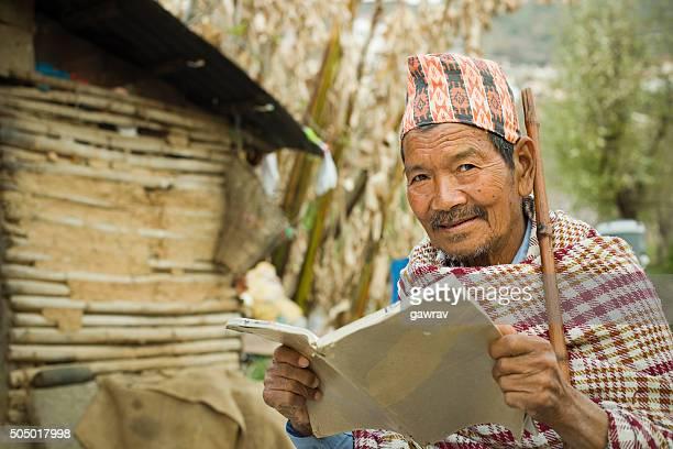 読書をする老人男性の屋外およびカメラ目線ます。