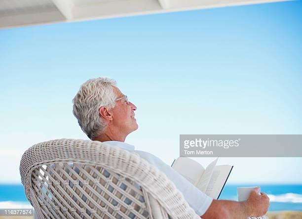 Älterer Mann liest ein Buch am Strand Terrasse