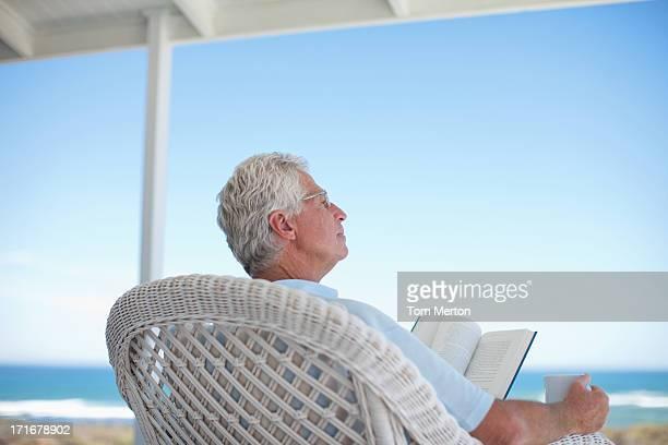 Uomo anziano legge un libro sulla spiaggia, con patio