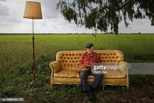 Senior man reading book on sofa in field