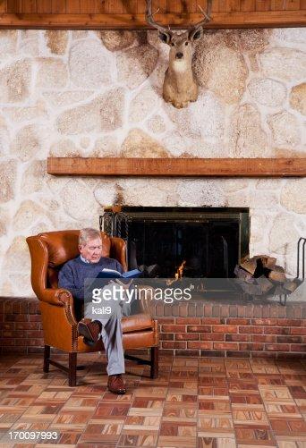 Senior man reading by fireplace