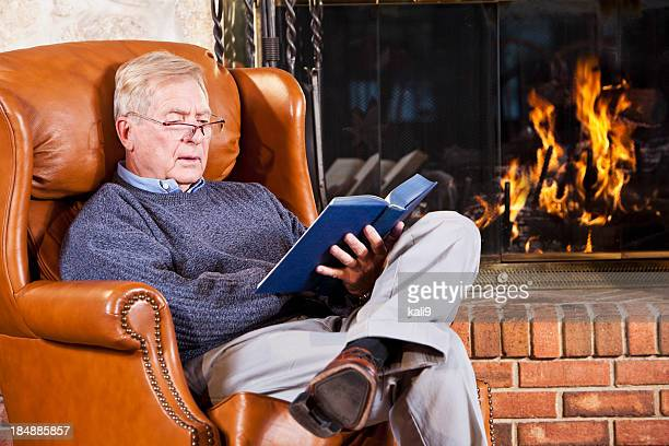 Senior man reading by fireplace