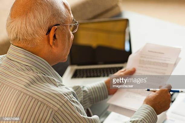 Senior man reading document near laptop on coffee table