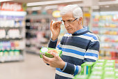 Elderly man shopping in local supermarket. He is holding box and reading nutrition label.