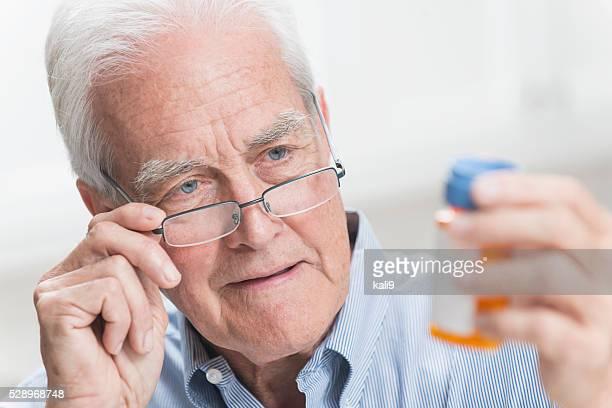 Senior man reading instructions on prescription bottle