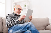Smiling senior man reading news on digital tablet. Cheerful excited mature male using portable computer at home, copy space