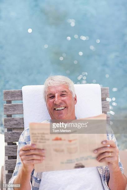 Homme âgé lisant un journal au bord de la piscine