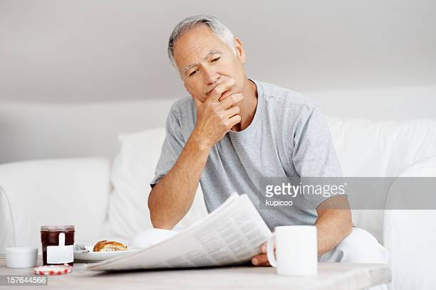 Uomo anziano, leggendo il giornale con la prima colazione nella tabella