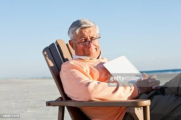 Uomo anziano leggendo sulla spiaggia