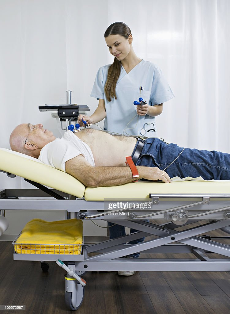senior man receiving electrocardiogram by nurse : Stock Photo