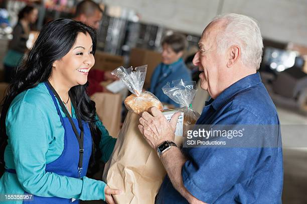 Senior man receiving food from volunteer