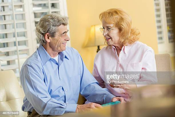 Senior man receiving prescription medication from wife at home