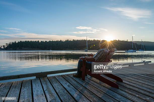 Senior man relaxes in chair, looks out across bay
