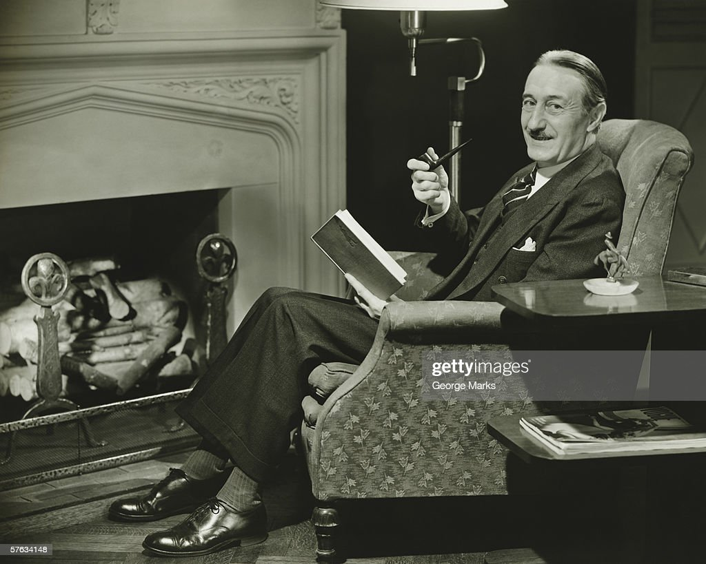 senior man relaxing in armchair at fireplace portrait stock photo