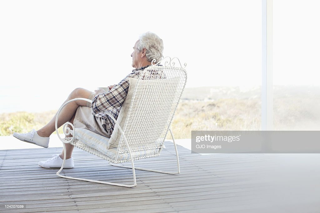 Senior man relaxing in chair on the porch : Stock Photo