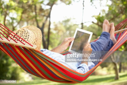 Senior Man Relaxing In Hammock With  E-Book : Stock-Foto