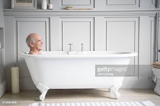Senior hombre relajante en blanco sonriendo tradicional de baño