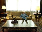 Senior man relaxing on sofa, propping feet on table