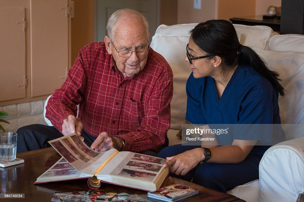 A senior man relives memories while looking at a photo album with a home health care nurse.