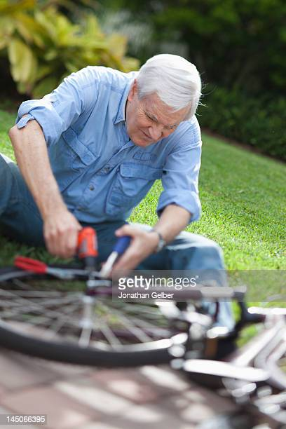 A senior man repairing a bicycle