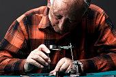 Senior man repairing old pocket watch